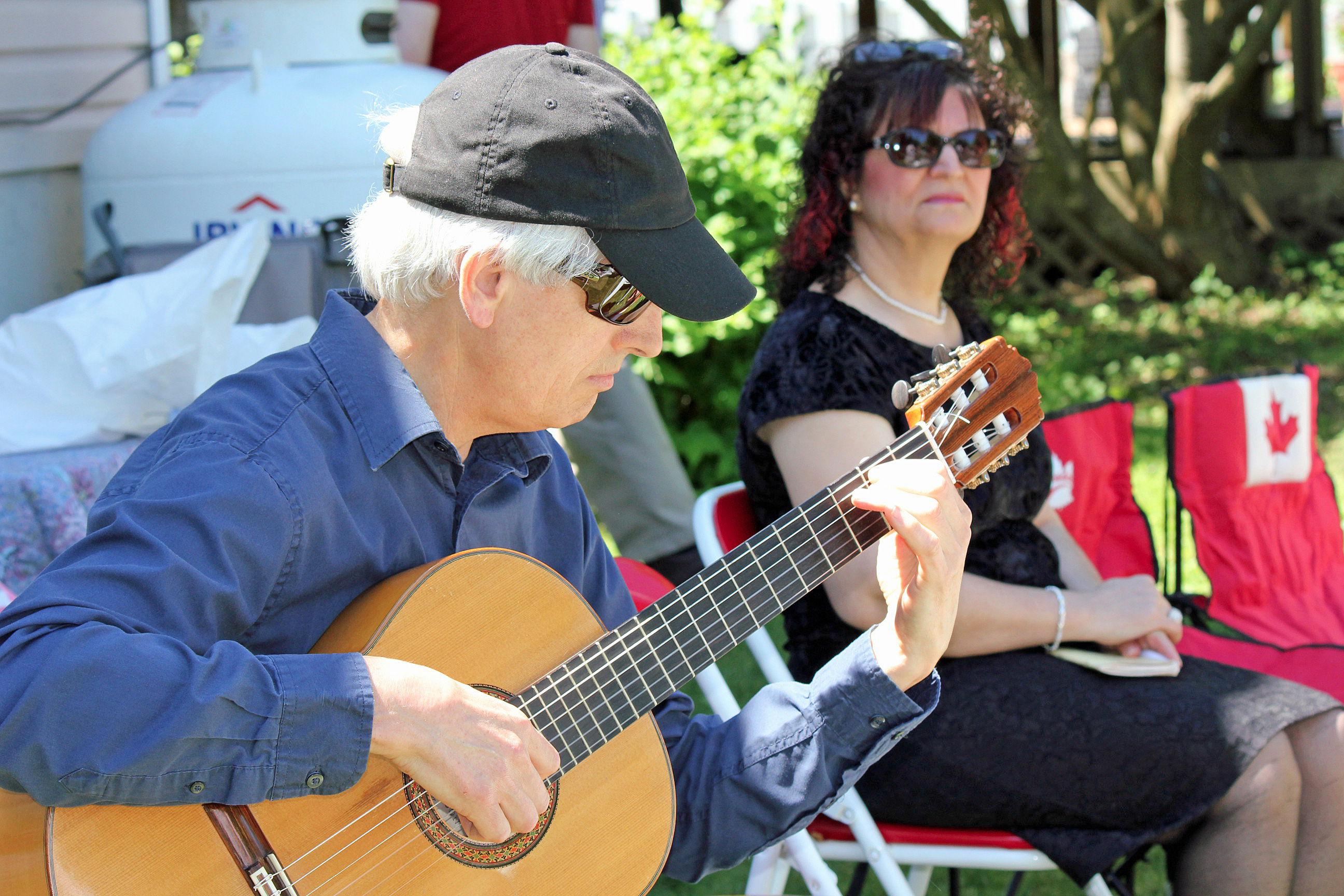 A Bahá'í plays guitar at a holy day commemoration in St. John's.